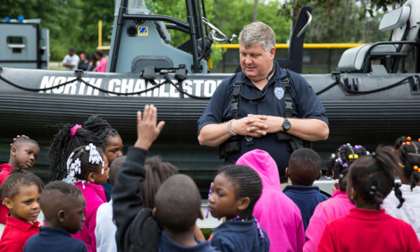 A police officer speaks with kids in North Charleston. Photo by Ryan Johnson.