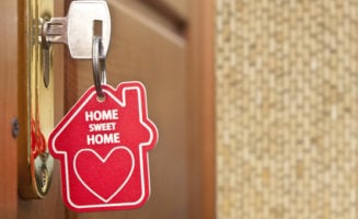 """Key in lock with """"Home Sweet Home"""" keychain. Photo by Shutterstock."""