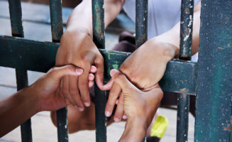 Hands Behind Bars photo from Shutterstock