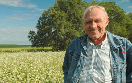 Fred Kirschenmann stands in a field.